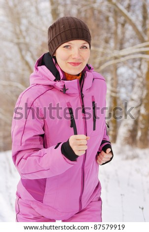 Young attractive girl running on a cold winter day - stock photo