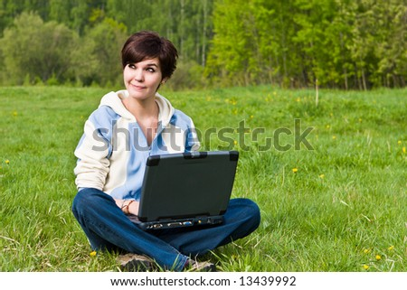Young attractive girl sits on a green grass with a portable computer