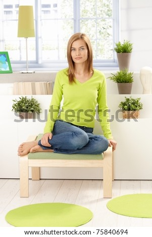 Young attractive girl sitting front of window, plants around, wearing vivid green pullover, smiling.? - stock photo