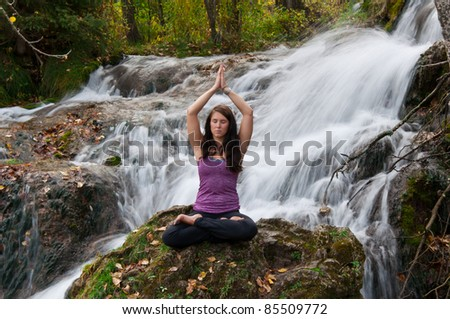 Young attractive girl sitting on a rock and meditating in a forest with a stream cascading down behind her.  The water is slowed and blurred to give a dreamy looking effect.