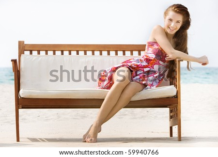 young attractive girl sitting on beach sofa over white - stock photo