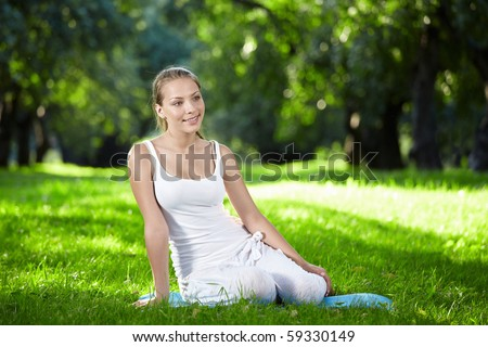 Young attractive girl sitting on the grass