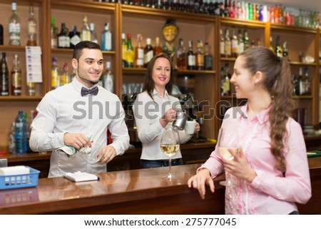 Young attractive girl standing at bar with glass of wine and flirting with barman. Focus on guy