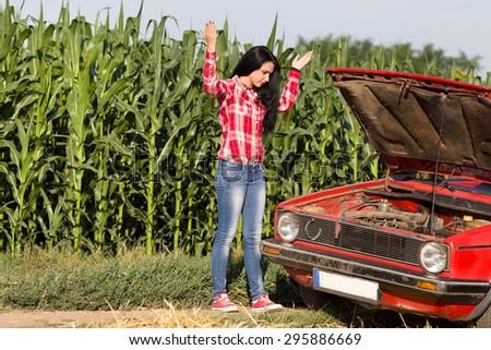 Young attractive girl standing beside broken car at rural road - stock photo