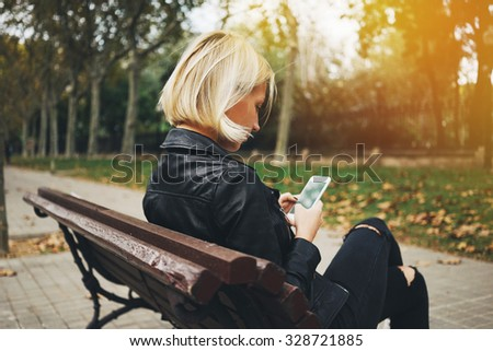 Young attractive girl using smartphone while sitting on a bench in the park, flare effects - stock photo