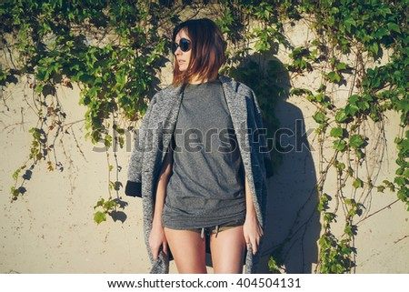 young attractive girl wearing a gray blank t-shirt and coat thrown over her shoulders posing on a background of a concrete wall with ivy - stock photo