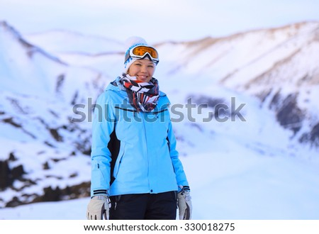 Young attractive girl wearing goggles and hat for winter sport at the mountains - stock photo