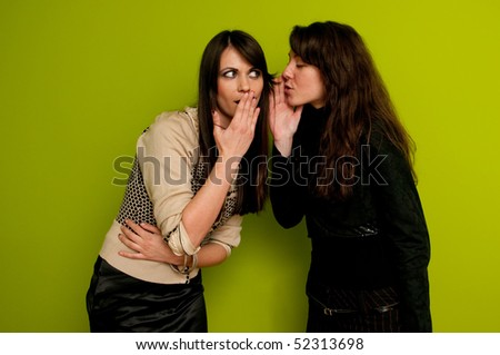 Young attractive girl whispering to her friend - stock photo