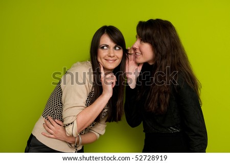 Young attractive girl whispering to her friend