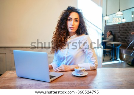 young attractive girl with curly hair working with a laptop computer in a coffee-shop.Beautiful female student searching information on the Internet.attractive girl in the interview during the lunch - stock photo