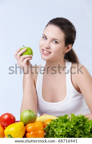 Young attractive girl with fruits and vegetables on white background - stock photo