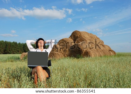 Young attractive girl with  laptop on  agricultural field - stock photo