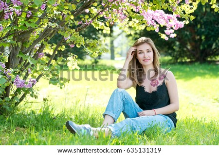 Young attractive girl with piercing on her nose. Woman in garden.