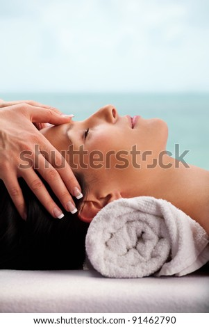 Young attractive girl,with pink flower, having head massage at spa resort.Sky added in post production - stock photo