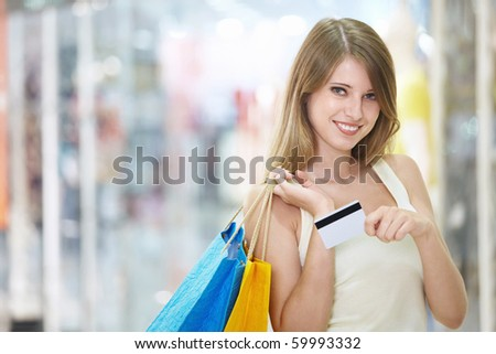Young attractive girl with shopping and credit card in store - stock photo