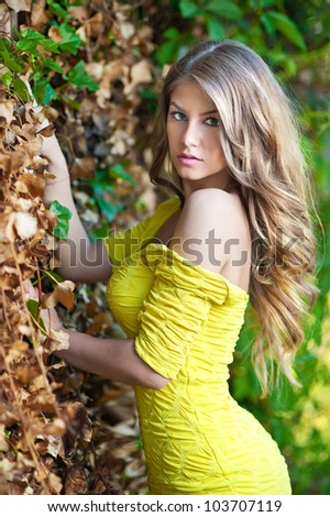Young attractive girl with yellow dress outdoor on the field.Golden pretty girl - stock photo