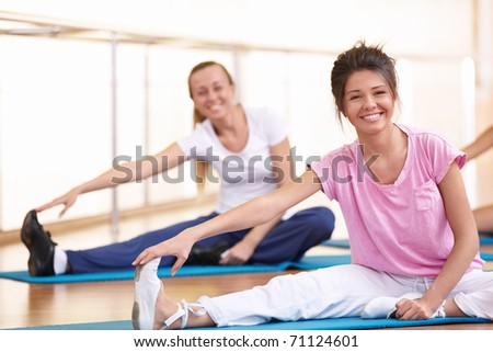 Young attractive girls doing stretching - stock photo