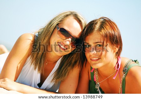 Young attractive girls enjoying together the summer beach