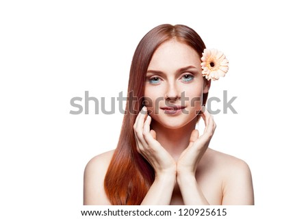 young attractive green-eyed red-haired caucasian female with beige gerbera flower in her gorgeous long natural straight shiny red hair which gently smiling and soft looking at camera - stock photo