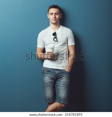 Young attractive handsome man in white t-shirt and jeans denim shorts standing against the wall and smiling holding coffee. - stock photo