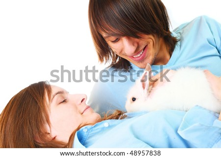 Young attractive happy amorous couple and rabbit at bedroom - stock photo