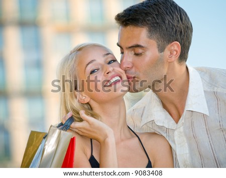 Young attractive happy amorous couple with shopping bags outdoors - stock photo