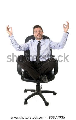 young attractive happy businessman relaxing with hands in yoga position looking cheerful and friendly wearing shirt and necktie isolated in white sitting on office chair in relax at work concept