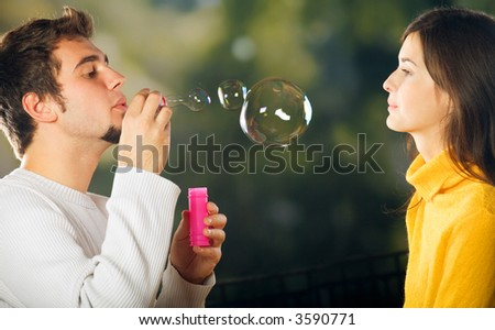 Young attractive happy couple blowing bubbles, outdoors - stock photo
