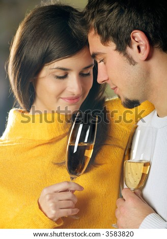 Young attractive happy couple celebrating event with champagne, outdoors