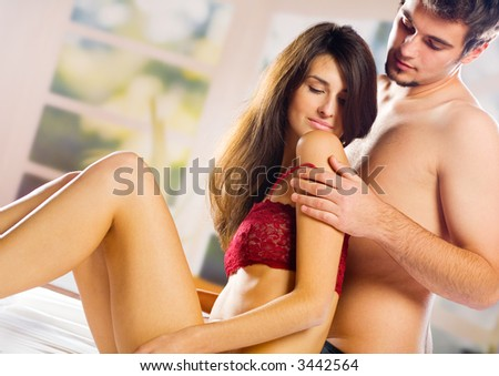Young attractive happy couple embracing in bedroom