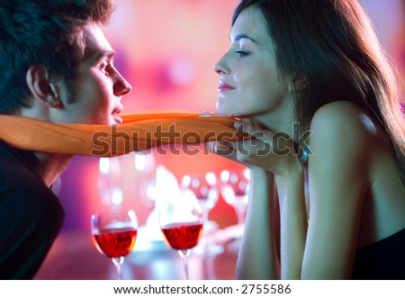 Young attractive happy couple kissing in restaurant, celebrating or on romantic date