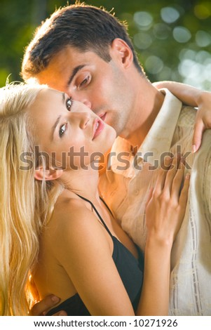 Young attractive happy love couple together, outdoors. Focus on woman.