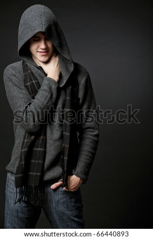 Young attractive happy man wearing gray sweater with hood.
