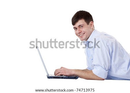 Young attractive happy man works lying with computer on floor. Isolated on white background. - stock photo