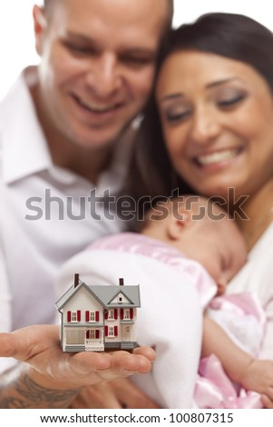 Young Attractive Happy Mixed Race Family with Baby and Small Model House. - stock photo