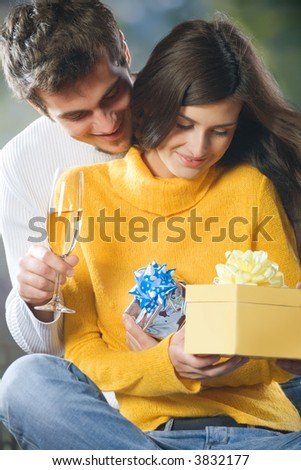 Young attractive happy smiling couple celebrating event with champagne and gift boxes, outdoors