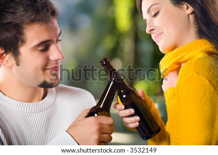 Young attractive happy smiling couple celebrating life event with beer, outdoors - stock photo