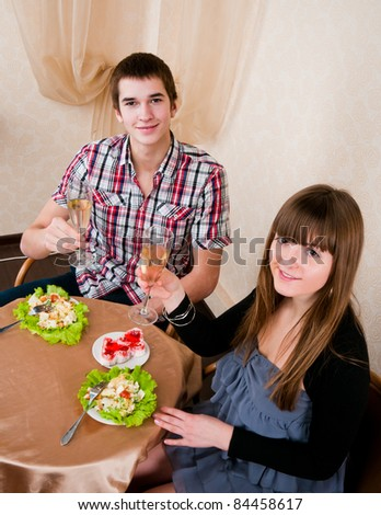 Young, attractive, happy, smiling couple celebrating with champagne, indoors