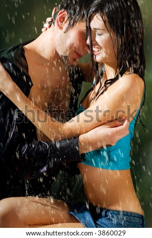 Young attractive happy smiling couple hugging under a rain, in passion - stock photo