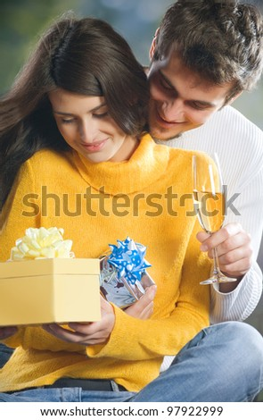 Young attractive happy smiling couple with champagne and gifts, outdoors - stock photo