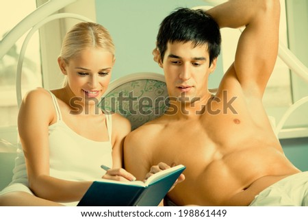 Young attractive happy smiling couple with notebook or organizer at home - stock photo