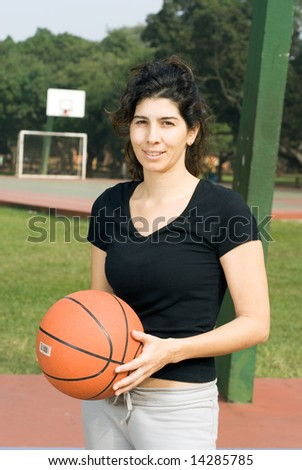 Young, attractive, happy woman is standing on an outdoor basketball court.  She is holding a basketball and looking at the camera.  Vertically framed shot. - stock photo
