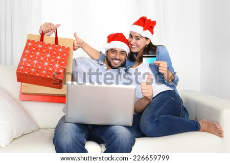 young attractive Hispanic couple in love together on sofa couch at home with computer laptop holding shopping bags purchasing online Christmas presents with credit card on internet e-commerce concept