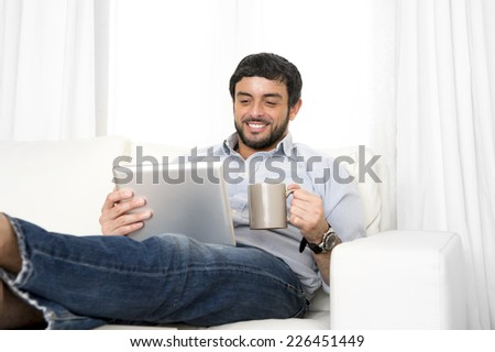 Young attractive hispanic man happy at home lying on couch using digital tablet or pad relaxed drinking coffee enjoying surfing internet watching online movie - stock photo