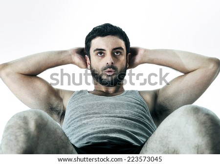 young attractive Hispanic sport man wearing running clothes doing sit up or crunch working abs and fitness workout isolated on white background in healthy lifestyle concept - stock photo
