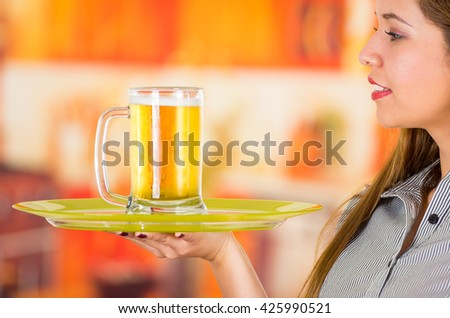 Young attractive holding a beer in bar - stock photo