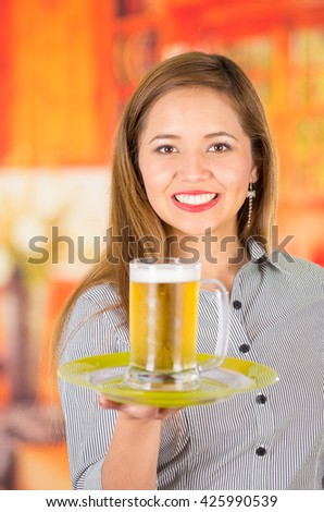 Young attractive holding a beer in bar, smiling - stock photo