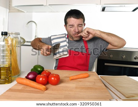 young attractive home cook man in red apron slicing carrot with kitchen knife  suffering domestic accident cutting and hurting his finger while cooking in pain face expression - stock photo