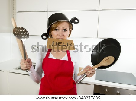 young attractive home cook woman in red apron at  kitchen holding pan and household with pot on her head in stress frustrated face expression in rookie amateur and inexperienced cooking concept - stock photo