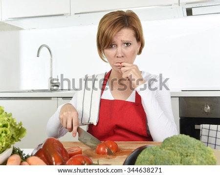 young attractive home cook woman in red apron slicing tomato with kitchen knife  suffering domestic accident cutting and hurting her finger while cooking in pain face expression licking blood - stock photo